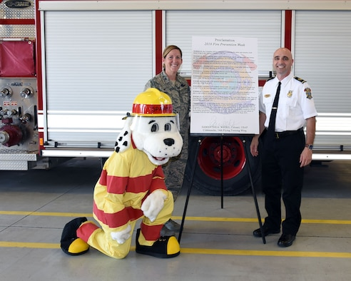 Col. Samantha Weeks, 14th Flying Training Wing commander, stands with Shawn Ricchuito, 14th Civil Engineering Squadron fire chief, and Sparky with the 2019 Fire Prevention Week proclamation, Sept 16, 2019, on Columbus Air Force Base, Miss. Columbus AFB will be hosting an open house and a parade on Oct. 5 to kick off Fire Prevention Week. (Courtesy Photo)