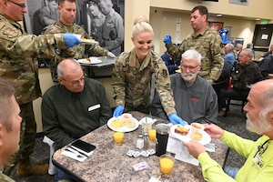 Senior Master Sgt. Erica Carruth, of the 119th Force Support Squadron, delivers breakfast dishes to retired unit members at the annual 119th Wing Chief's Council retiree breakfast at the North Dakota Air National Guard Base, Fargo, N.D., Oct. 2, 2019.