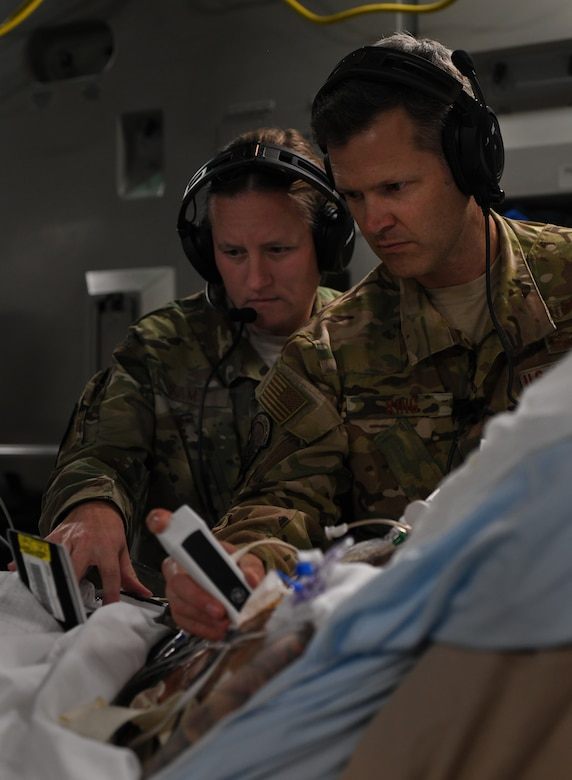 Lt. Col. Valerie Sams, 59th Medical Wing trauma surgeon, and Lt. Col. Scott King, 86th Aeromedical Evacuation Squadron critical care air transport team physician, perform an ultrasound on a critically wounded service member during a flight from Bagram Airfield, Afghanistan to San Antonio, Texas, Aug. 18, 2019. The service member suffered extensive wounds during combat operations that required constant monitoring over the duration of a 20-hour direct flight from Afghanistan to Texas. (U.S. Air Force photo by Airman 1st Class Ryan Mancuso)