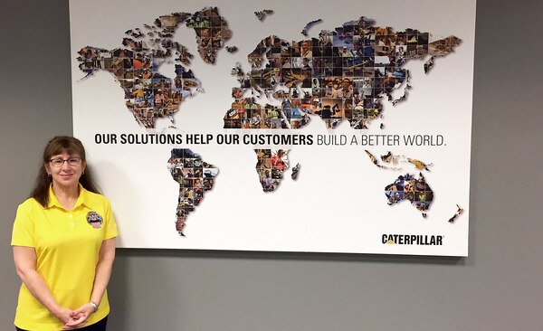 "Woman in yellow DLA shirt stands in front of Caterpillar's map with the slogan, ""Our solutions help our customers build a better world."""