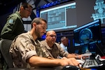(From left) Brazilian Air Force Maj. Rafael de Almeida Duque, Brazilian Aerospace Command, collaborates with Spanish Air Force members at Lockheed Martin's Center for Innovaton in Suffolk, Va., Sept. 27, 2019, during Global Sentinel 19. During the week, each participating nation maintained a space operations center (SpOC) to command and control their SSA space situational awareness.  (U.S. Air Force photo by Staff Sgt. J.T. Armstrong)