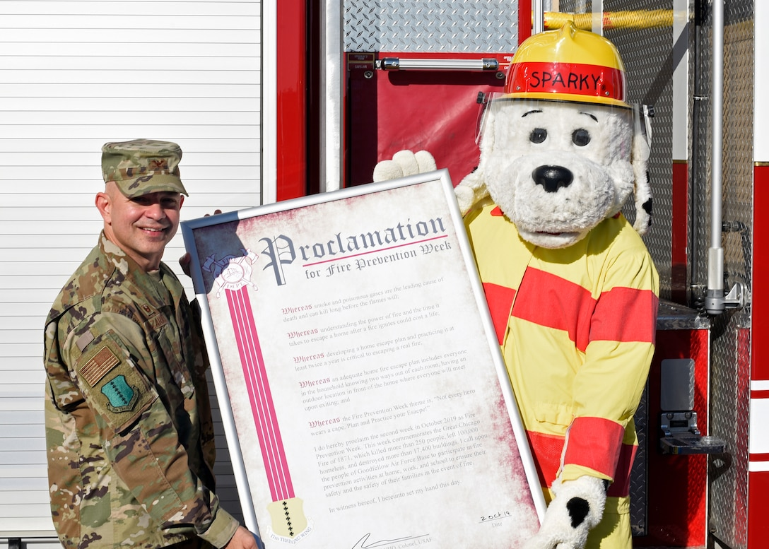 """U.S. Air Force Col. Andres Nazario, 17th Training Wing commander, stands with Sparky, fire prevention mascot, after signing the Fire Prevention Week proclamation at the Norma Brown building on Goodfellow Air Force Base, Texas, Oct. 2, 2019. The theme of this year's Fire Prevention Week is """"Not every hero wears a cape"""". (U.S. Air Force photo by Air Force photo by Airman 1st Class Zachary Chapman/Released)"""