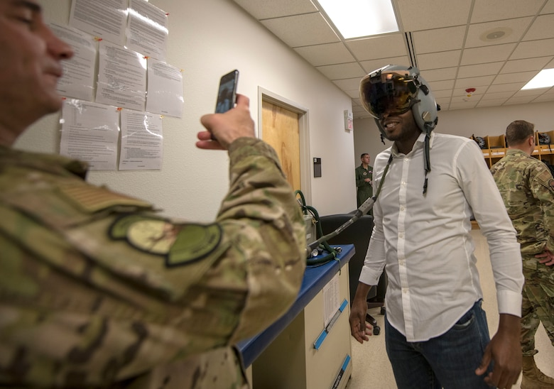 Col. Joseph Campo, 49th Wing commander, takes a photo of Yves Zamar, congressional staff representative for Congresswoman Deb Haaland, in a helmet, Oct 2, 2019, on Holloman Air Force Base, N.M. Staffers visited to better understand the Holloman mission and its role within New Mexico. (U.S. Air Force photo by Staff Sgt. Christine Groening)