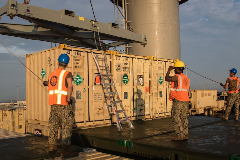 Sailors in protective helmets and orange vests hold guide lines attached to a crane that is preparing to lift a shipping container.