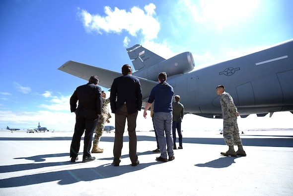Men in suits along with men in military uniforms look out on the tail of a KC-10 Extender on a long expanse of runway