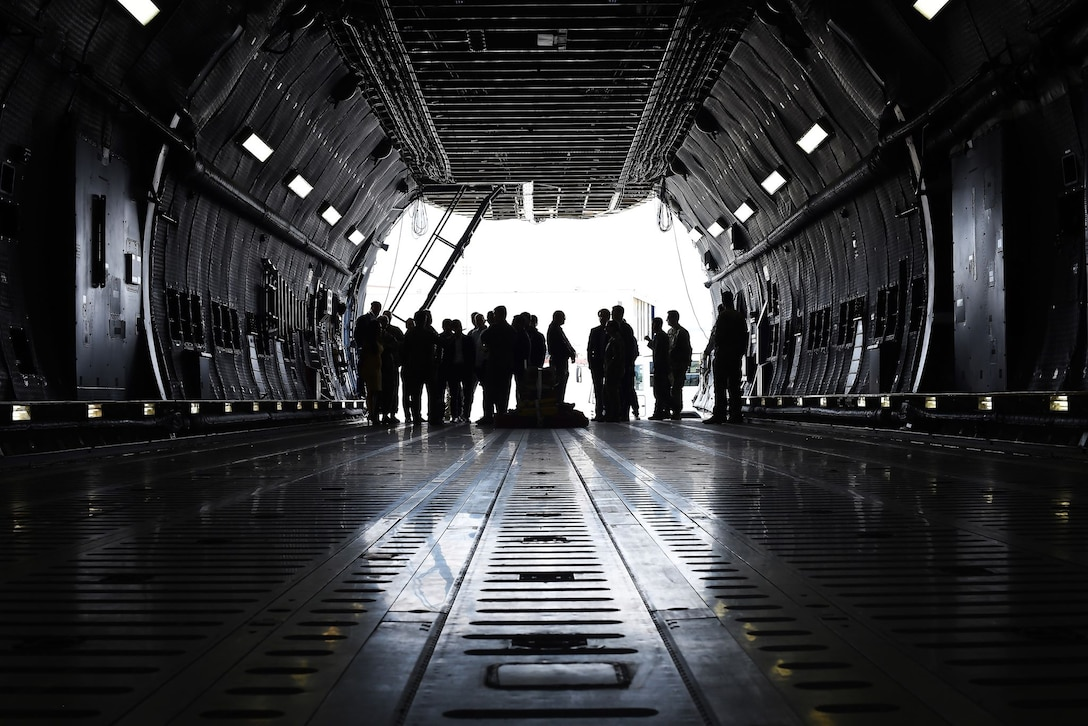 A gaggle of civilians and military members are silhouetted against the bright sunlight outside of the C-5M Super Galaxy in which they currently stand