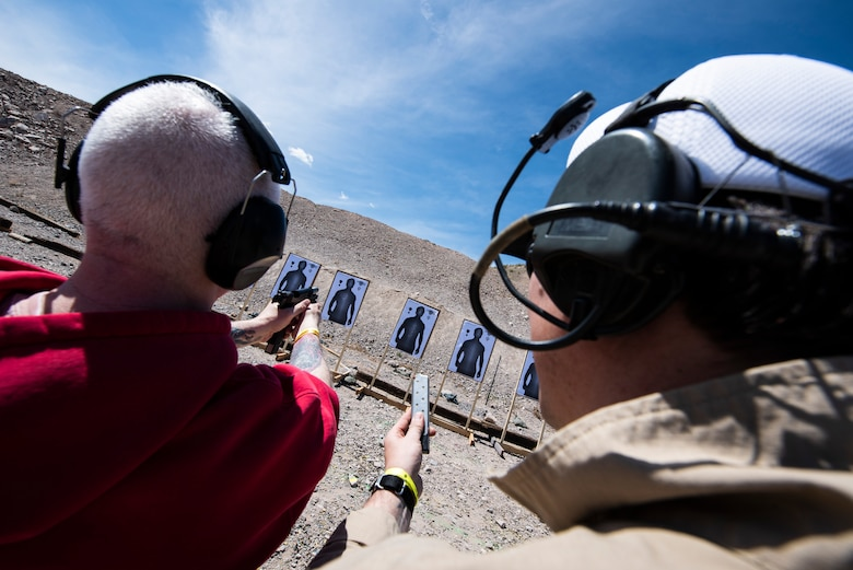 John Ferrelli, an information system security manager assigned to the 99th Communications Squadron (CS), fires a handgun at an undisclosed location in Las Vegas, April 3, 2019. Annual award winners from the 99th CS received combat tactics training as part of the Invictus Experience. (U.S. Air Force photo by Staff Sgt. Joshua Kleinholz)