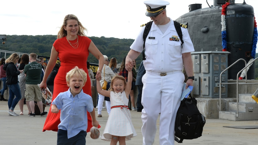 A sailor walks with a woman and two laughing kids.