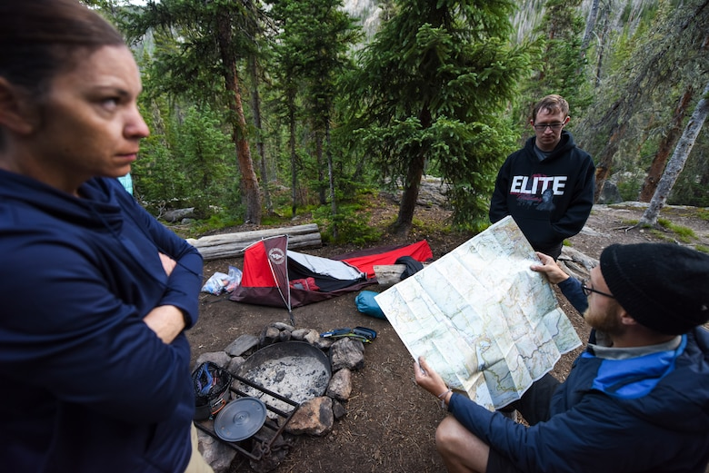 U.S. Air Force Master Sgt. Aimee Klarmann and Senior Airman Justin Sharp, 99th Communications Squadron annual award winners, survey a park map with their guide during a backpacking trip across the Continental Divide in Rocky Mountain National Park, Colorado, July 19, 2019. The trip covered 26 miles and exposed the Airmen to four natural biomes. (U.S. Air Force photo by Staff Sgt. Joshua Kleinholz)