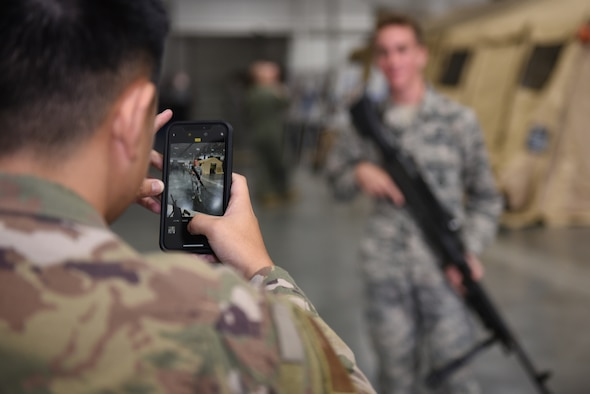 U.S. Air Force Airman 1st Class Brandon Pharn, 821st Contingency Response Squadron force protection team member, takes a photo of Airman Ezra Ashton, 60th Security Forces Squadron patrolman, holding an M-240B machine gun during the Airmen Enrichment Program Sept. 27, 2019, at Travis Air Force Base, California. The program offers Airmen the opportunity to learn about the numerous specialties the Air Force has to offer. (U.S. Air Force photo by Airman 1st Class Cameron Otte)