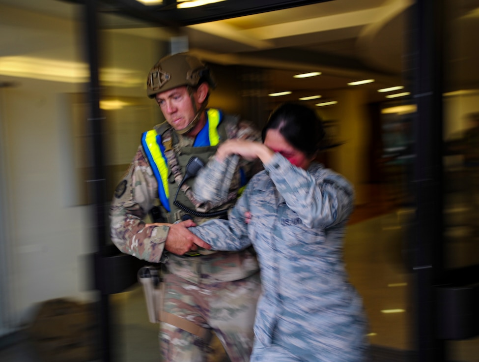 A U.S. Airmen assigned to the 86th Security Forces Squadron escorts a simulated victim out of a building at Ramstein Air Base, Germany, Sept. 25, 2019. The defender responded to a mass casualty event that was part of Operation Varsity 19-03, a weeklong exercise designed to test the capabilities of Ramstein Airmen. (U.S. Air Force photo by Tech. Sgt. Timothy Moore)