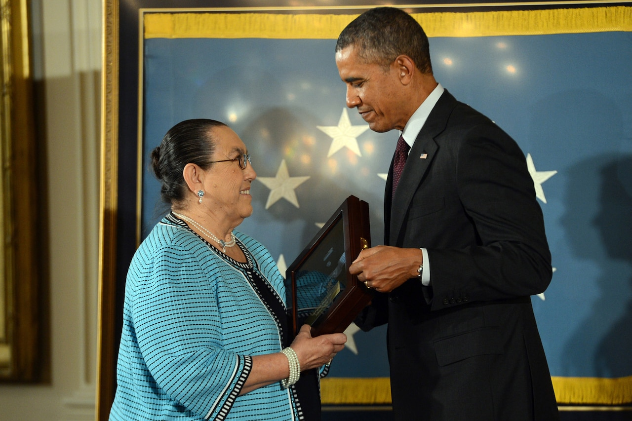 A woman wearing a dress and glasses smiles as she accepts the Medal of Honor, encased in a wooden box with a glass top, from former President Obama.