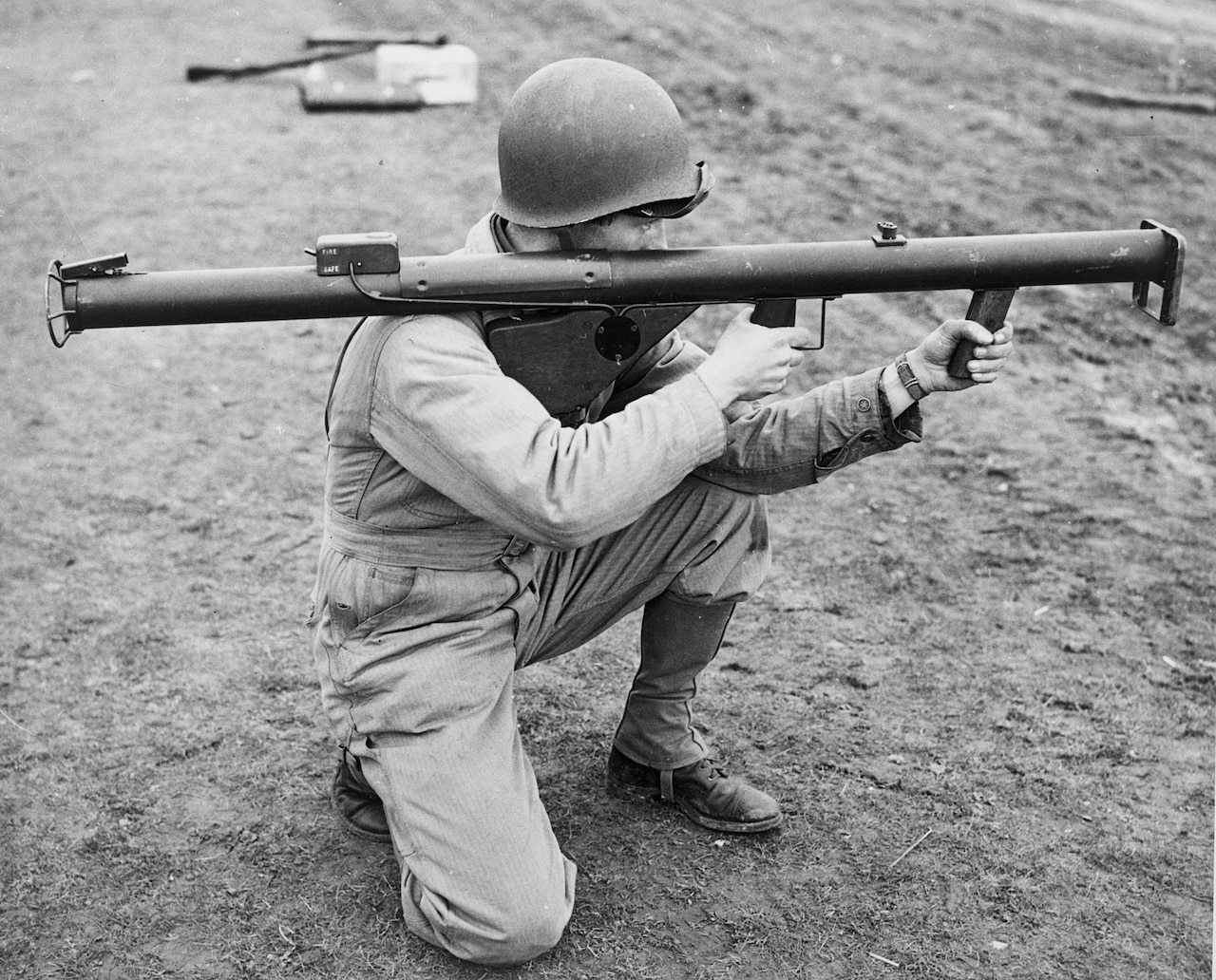 A World War II Army infantry soldier holds a first-generation grenade launcher.