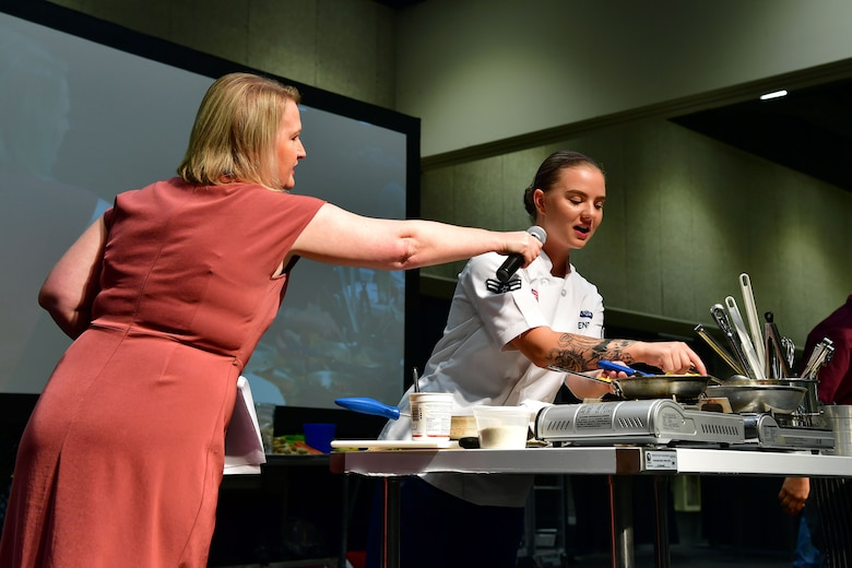 An Airman answers questions from the announcer during the Iron Chef Championship competition.