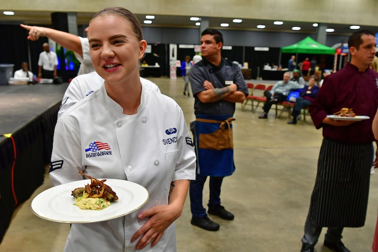 An Airman waits to hand her dish to the judges.