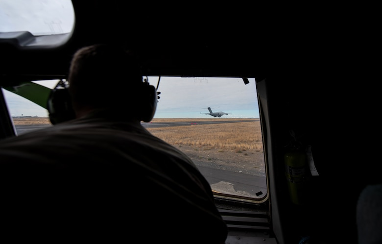 U.S. Army Col. Skye Duncan, Joint Base Lewis-McChord (JBLM) commander, watches a C-17 Globemaster III take off through the window of another C-17 at Moses Lake Municipal Airport, Wash., Oct. 1, 2019. The purpose of the flight was to provide training opportunities for Air Force pilots and Army Soldiers during a mobility movement exercise. (U.S. Air Force photo by Senior Airman Tryphena Mayhugh)