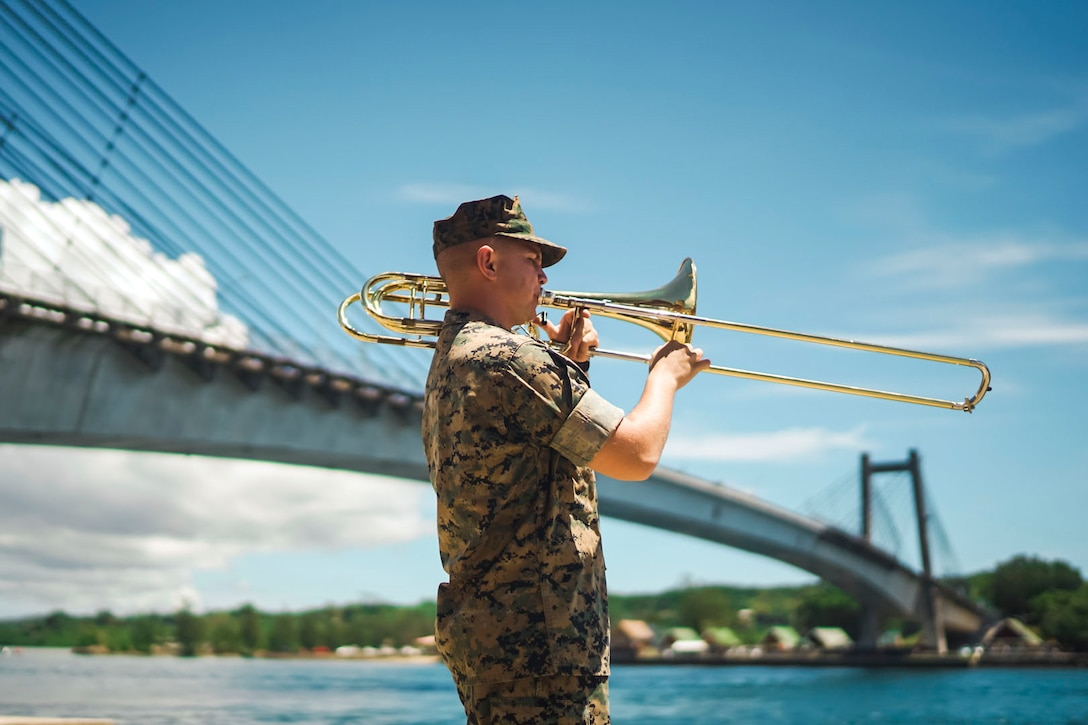 A Marine plays an instrument with a large bridge in the background.