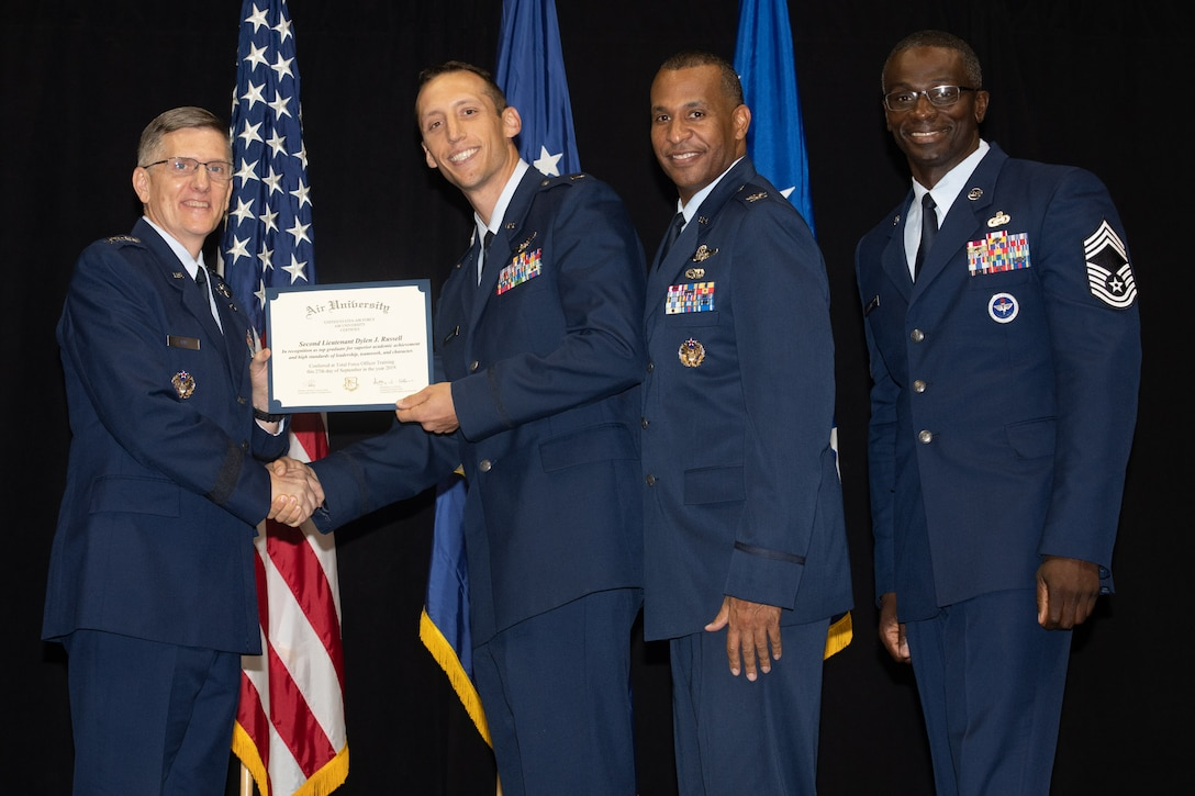 """Gen. Tim Ray, Air Force Global Strike Command commander, presents the top graduate award for the 24th Training Squadron to 2nd Lt. Dylan Russel from Air University's Officer Training School """"Godzilla"""" class 19-07 during an awards ceremony at the Alabama State University Acadome, Montgomery, Ala., Sept. 26, 2019. Class 19-07, dubbed internally as """"Godzilla,"""" started with more than 800 officer trainees, effectively double the average class size."""