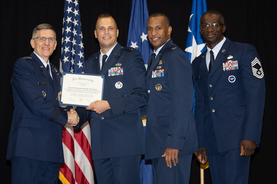 """Gen. Tim Ray, Air Force Global Strike Command commander, presents the top graduate award for Detachment 12 to 2nd Lt. Timothy Dijone from Air University's Officer Training School """"Godzilla"""" class 19-07 during an awards ceremony at the Alabama State University Acadome, Montgomery, Ala., Sept. 26, 2019. Class 19-07, dubbed internally as """"Godzilla,"""" started with more than 800 officer trainees, effectively double the average class size."""