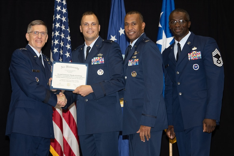 "Gen. Tim Ray, Air Force Global Strike Command commander, presents the top graduate award for Detachment 12 to 2nd Lt. Timothy Dijone from Air University's Officer Training School ""Godzilla"" class 19-07 during an awards ceremony at the Alabama State University Acadome, Montgomery, Ala., Sept. 26, 2019. Class 19-07, dubbed internally as ""Godzilla,"" started with more than 800 officer trainees, effectively double the average class size."