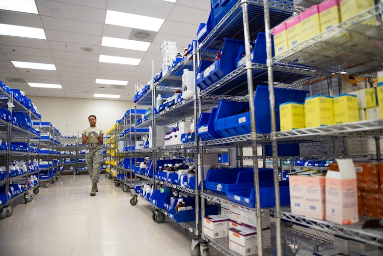 A pharmacy technician walks down an isle contain bottles medication on each side.