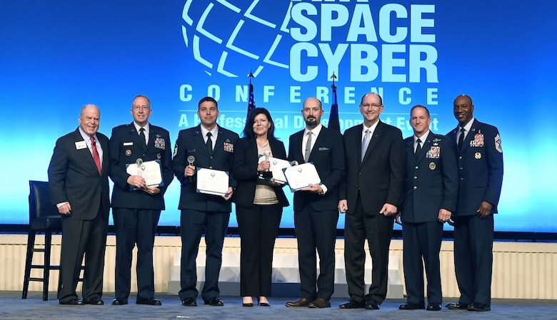Lt. Col. Andrew Allen, Master Sgt. Kyle Wilson, Jean-Anne Butler and Matthew Bradesca receive the International Affairs Excellence Award from Air Force Chief of Staff Gen. David L. Goldfein, Acting Secretary of the Air Force Matthew Donovan, Chief Master Sgt. of the Air Force Kaleth Wright and Whit Peters, Chairman of the Air Force Association Board, during the Air Force Association Air, Space and Cyber Conference Sept. 16, 2019, in National Harbor, Md.