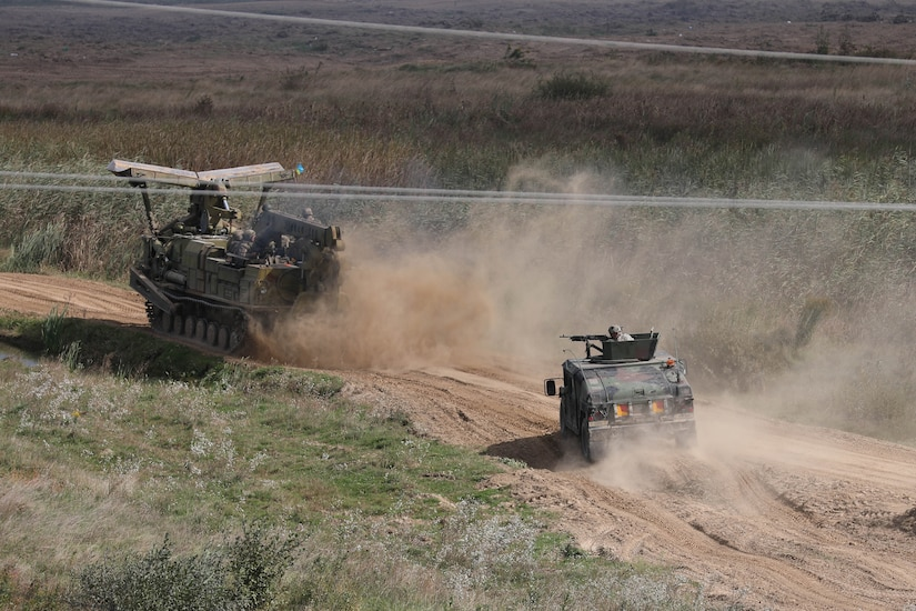 Two military combat vehicles traverse a dirt path.
