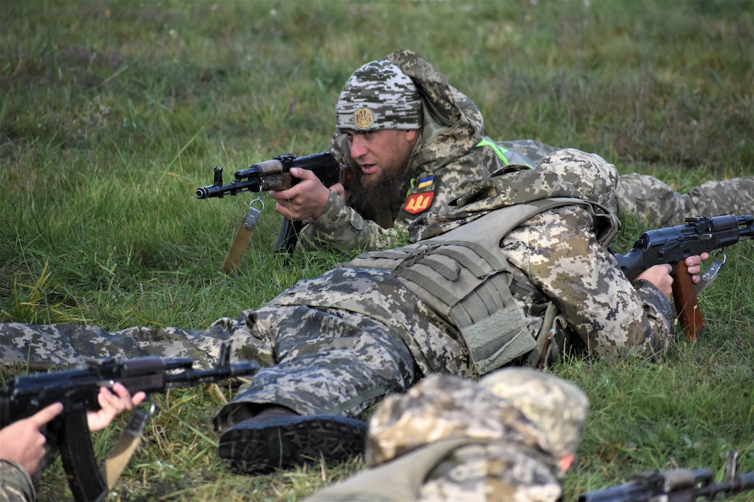 Soldiers lie on the ground and aim their rifles.