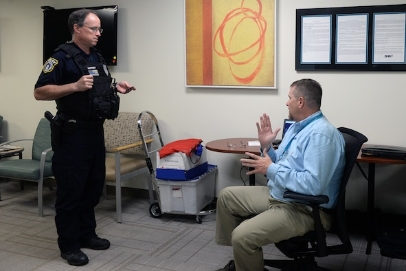 David Conrad VA outreach coordinator sits right and speaks to Police officer James Munsey about VA benefits.