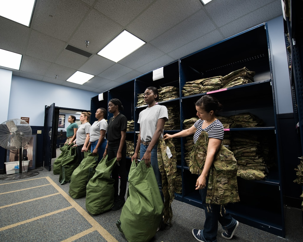Cecil Harvey, 502d Logistics Readiness Squadron lead supply technician, helps a U.S. Air Force basic military training trainee, 326th Training Squadron, during the initial issue of the first operational camouflage pattern (OCP) uniform, Oct. 2, 2019, at Joint Base San Antonio-Lackland, Texas.