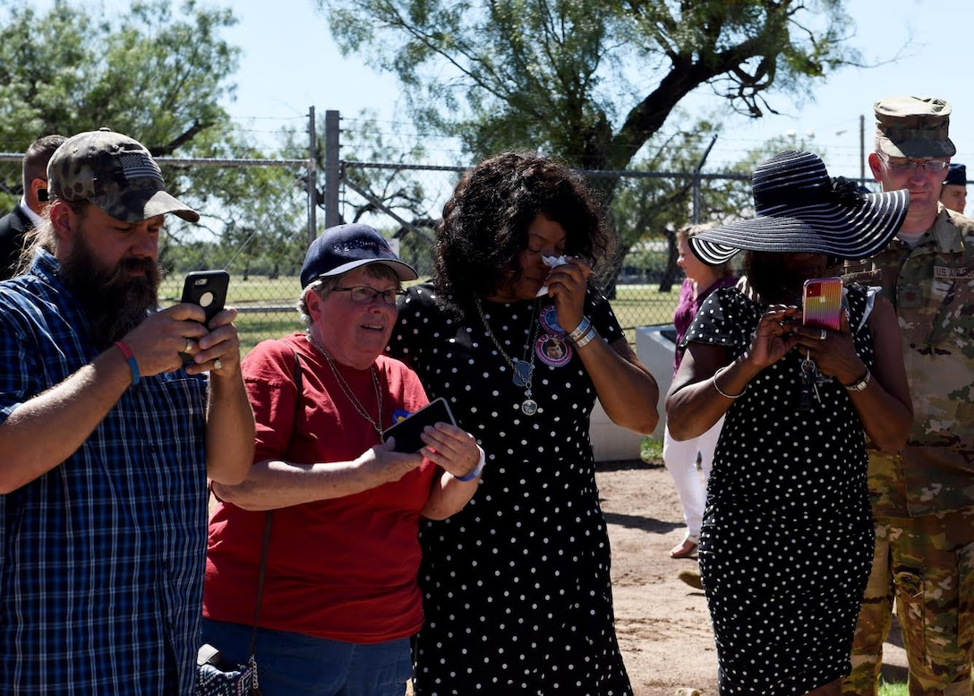 Family members of fallen Airmen from TORQE 62 take photos of a memorial in Abilene, Texas, Oct. 2, 2019.