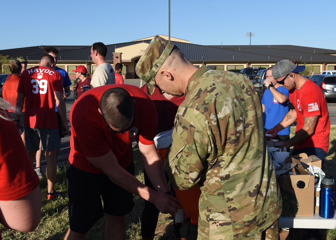Airmen assigned to Dyess Air Force Base, Texas, stop for water after finishing their run in the TORQE 62 memorial run Oct. 2, 2019.