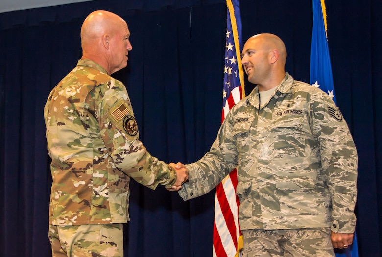 Gen. Jay Raymond, U.S. Space Command and Air Force Space Command commander, coins Staff Sgt. Michael Toderick, 61st Medical Squadron's non-commissioned officer in charge of community health, while visiting the Space and Missile Systems Center (SMC), Los Angeles Air Force Base, El Segundo, Calif., Oct. 1, 2019. During his visit, Gen. Raymond spoke with Airmen about the recent standup of U.S. Space Command and the critical role SMC plays in speeding up the acquisition process and delivering space capabilities.