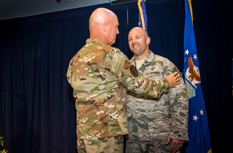 Gen. Jay Raymond, U.S. Space Command and Air Force Space Command commander, promotes SSgt Michael Toderick, 61st Medical Squadron non-commisioned officer in charge of community health, to the rank of Tech. Sgt. as a part of the Stripes for Exceptional Performers program (STEP), while visiting the Space and Missile Systems Center, Los Angeles Air Force Base, El Segundo, Calif., Oct. 1, 2019. The STEP program identifies and promotes the Air Force's best performing Airmen. Each calendar year, major commands, Field Operating Agency and Direct Reporting Unit commanders, and senior Air Force officers with large enlisted populations are authorized to select a limited number of Airmen with exceptional potential for promotion to the ranks of Staff and Tech. Sgt. STEP-promotions are a rare honor and Gen. Raymond had only one stripe to give this year for the entire Command. (U.S. Air Force photo by Van De Ha)
