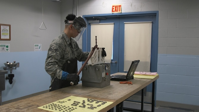 Senior Airman Brandon Dinh, an electro-environmental technician from the 446th Maintenance Squadron at Joint Base Lewis-McChord, Wash., demonstrates use of the Battery Cell Extraction Tool.  Airmen at the 446th MXS entered the newly forged tool in the Spark Tank 2020 competition.