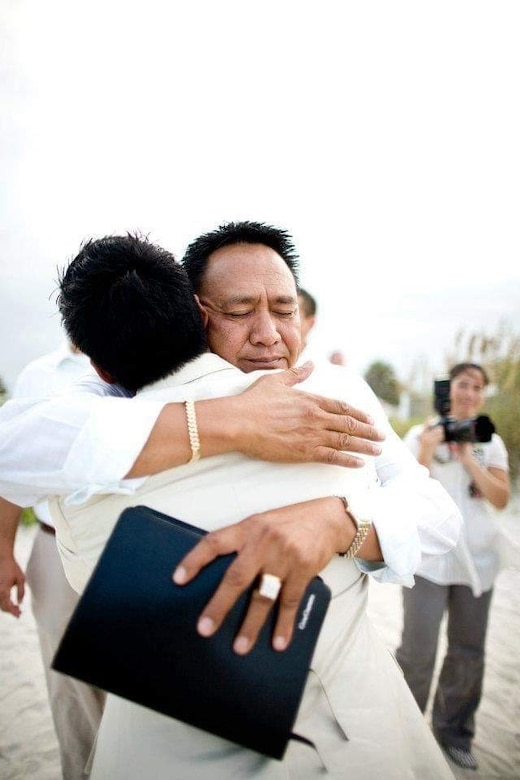 U.S. Air Force Capt. Genesis Guerrero, now a chaplain for the 39th Air Base Wing, (front) receives a hug from his father, Gene (face shown), on his wedding day, Aug. 1, 2009, at St. Augustine, Fla. As a chaplain, Guerrero draws inspiration from his experience in forgiving his father's troubled lifestyle, and seeks to help Airmen find peace through forgiveness and reconciliation, (Courtesy photo)