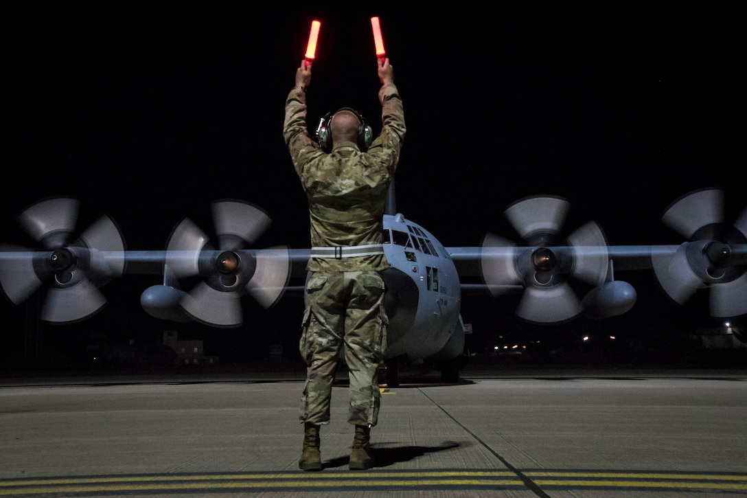 Photo of an Airman waving directions to a moving C-130 on the flight line during early morning.