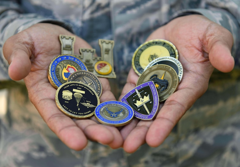 Airman 1st Class Saeed Shnawa, an aircrew flight equipment technician assigned to the 811th Operations Support Squadron on Joint Base Andrews, Md., displays his commemorative coin collection on base, June 6, 2019. Shnawa received coins and letters of commendation for his work with the U.S. and coalition forces during Operation Iraqi Freedom. (U.S. Air Force photo by Senior Airman Alyssa D. Van Hook)