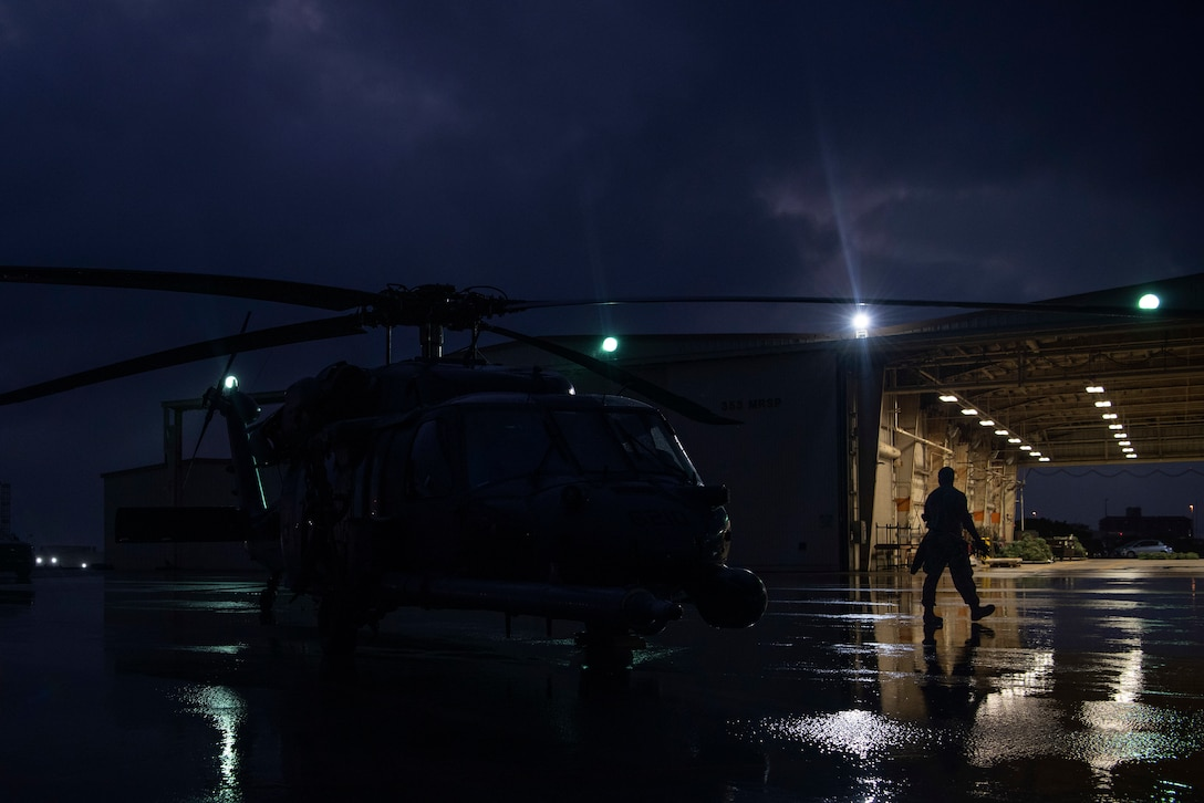 U.S. Air Force Senior Airman Andre Butler, 33rd Rescue Squadron crew chief, walks back to his squadron after completing preflight inspections of an HH-60 Pave Hawk Sept. 19, 2019, at Kadena Air Base, Japan. The HH-60 Pave Hawk has a hoist capable of lifting up to 600 pounds during personnel recovery missions. (U.S. Air Force photo by Senior Airman Rhett Isbell)
