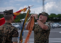 U.S. Marine Col. Michael J. Roach, Commanding Officer of 12th Marine Regiment, 3rd Marine Division, attaches a streamer to colors during the 12th Marine Regiment 92nd Anniversary Battle Colors Rededication Ceremony on Camp Hansen, Okinawa, Japan, Oct. 4, 2019. The ceremony is an opportunity for Marines to remember warriors past and to recognize contributions of service members and families to current operations. (U.S. Marine Corps photo by Lance Cpl. D'Angelo Yanez)
