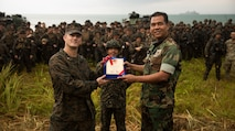 U.S. Marine Lt. Col. Todd Jacobs, the Commander of Toops for 3rd Marine Division during exercise Tiger Strike 19, presents a gift to the Malaysian Armed Forces at Blue Beach, Malaysia, on Oct. 2, 2019. Tiger Strike 19 focuses on strengthening joint military interoperability and on increasing readiness by practicing for humanitarian assistance, disaster relief, amphibious and jungle warfare operations, all while fostering cultural exchanges between the MAF and the U.S. Navy, Marine Corps team. (U.S. Marine Corps photo by Cpl. Josue Marquez)