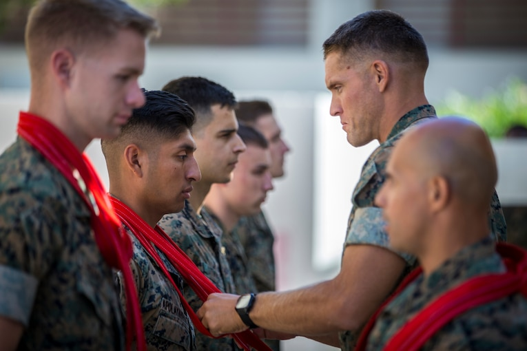 A Marine places a red scarf around the neck of another Marine.