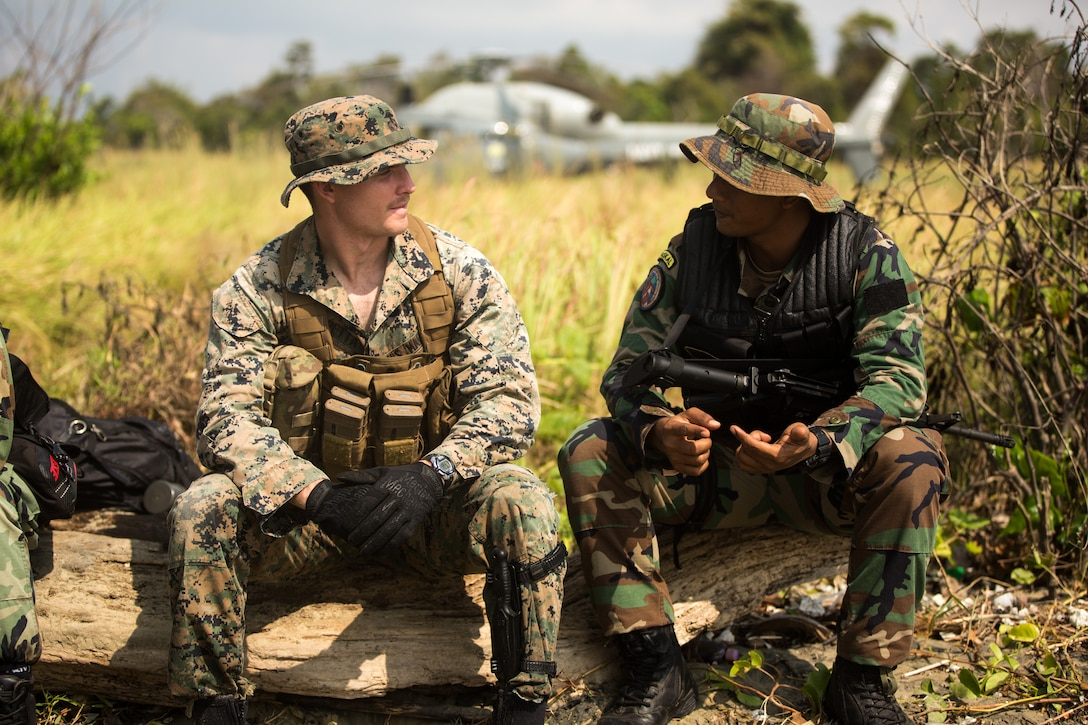 U.S. Marine Cpl. Aaron Petta, a reconnaissance marine with B Company, 3rd Reconnaissance Battalion, 3rd Marine Division, meets a member of the Malaysian Armed Forces' Royal Malaysian Navy at Blue Beach, Malaysia, on Sept. 30, 2019. The two were exchanging and comparing their personal military experiences with one another. Tiger Strike 19 allows U.S. Marines and Sailors to train side-by-side with our Malaysian partners, increasing combat readiness and improving bilateral coordination so both nations are best able to respond to crisis in the Indo-Pacific.