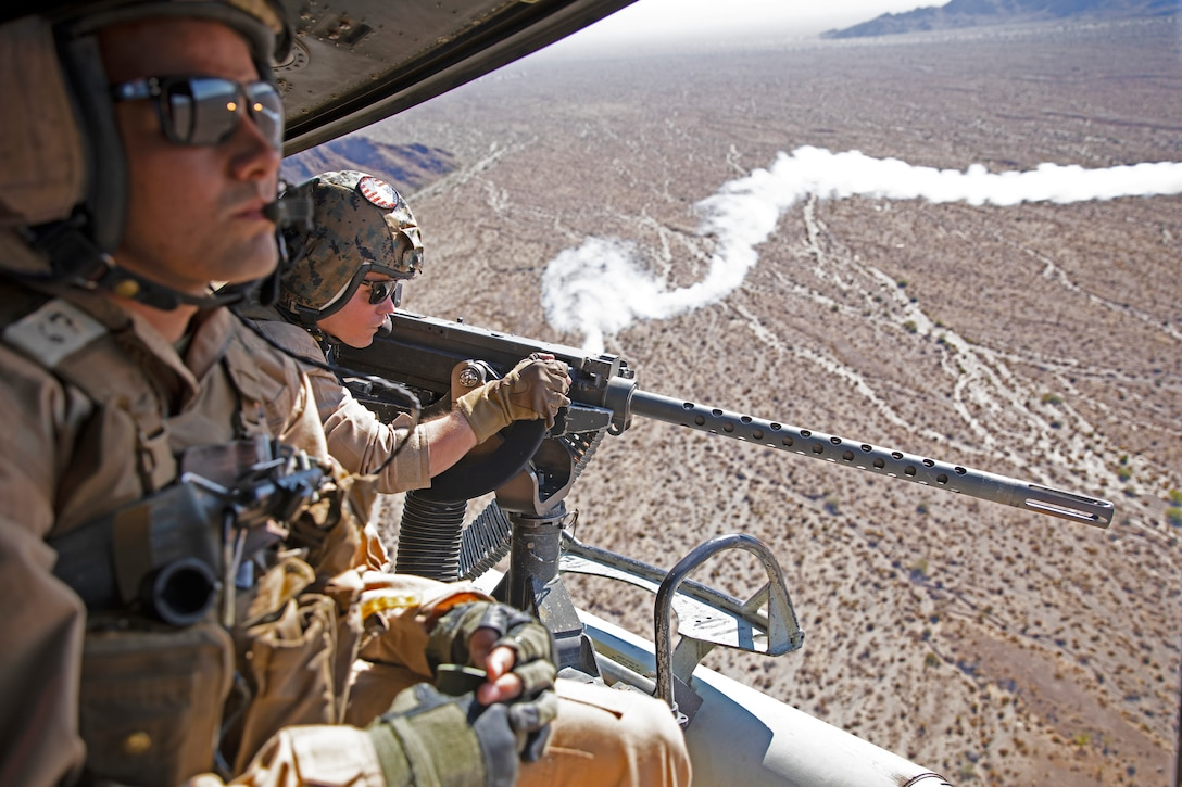 U.S. Marine Corps Cpl. Ross Roby, right, a UH-1Y Venom crew chief, with Marine Light Attack Helicopter Squadron 367, Marine Aircraft Group 39, 3rd Marine Aircraft Wing, engages targets while conducting an offensive air support exercise during Weapons and Tactics Instructor course 1-20 at Chocolate Mountain Aerial Gunnery Range, California, Sept. 30, 2019. WTI is a seven-week training event hosted by Marine Aviation Weapons and Tactics Squadron One, which emphasizes operational integration of the six functions of Marine Corps aviation in support of a Marine Air Ground Task Force. WTI also provides standardized advanced tactical training and certification of unit instructor qualifications to support Marine aviation training and readiness, and assists in developing and employing aviation weapons and tactics.