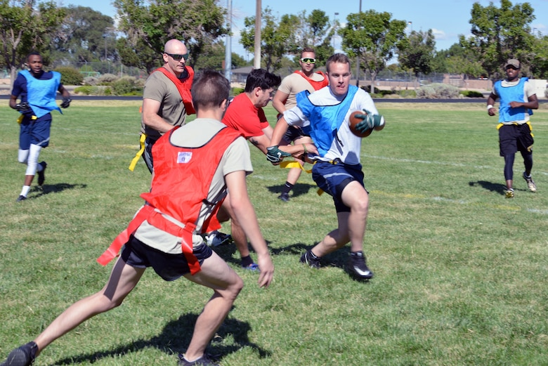 Members of the 58th Special Operations Wing play flag football during the 2019 58 SOW Sports Day at Kirtland Air Force Base, N.M., Sept. 27, 2019. Other sports played throughout the day included basketball, kickball, volleyball and more. The sports day included a competition between all the squadrons in the wing with top placements in every sport earning points for the unit. The 58th Aircraft Maintenance Squadron won the competition with almost double the points of the second place squadron.