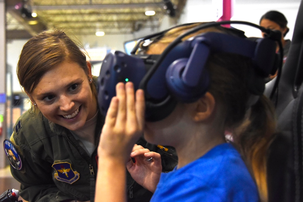 An airman looks at a child wearing a headset.