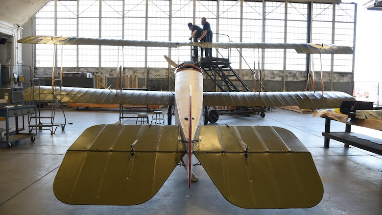 Top wing of biplane being worked on during restoration.