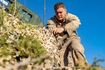 U.S. Marine Corps Lance Cpl. Trevor Kunz, a team leader with 3rd Light Armored Reconnaissance Battalion, 1st Marine Division, attaches camouflage netting to a Light Armored Vehicle during a Marine Corps Combat Readiness Evaluation (MCCRE) at Marine Corps Air Ground Combat Center Twentynine Palms, California, Sept. 6, 2019. The MCCRE is used to formally evaluate Marines on their combat readiness prior to their upcoming deployment. (U.S. Marine Corps photo by Lance Cpl. Roxanna Ortiz)