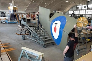 Restoration crew members working on biplane wing during restoration.