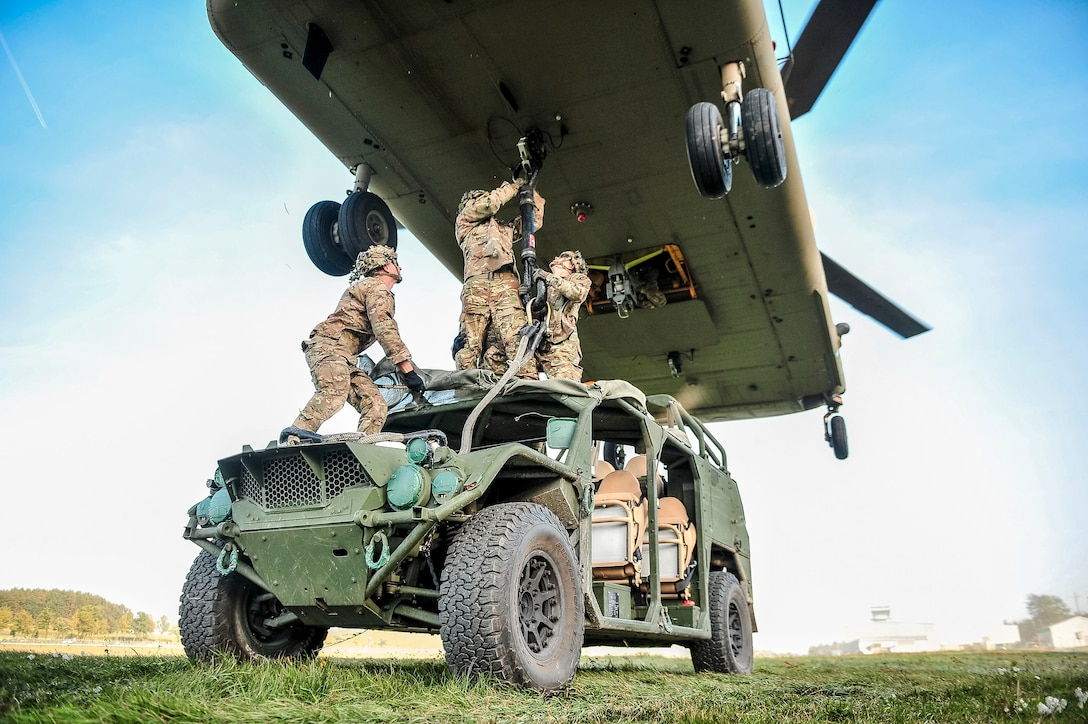 Soldiers stand on top of a tactical vehicle and attach it by sling to a helicopter's underbelly.
